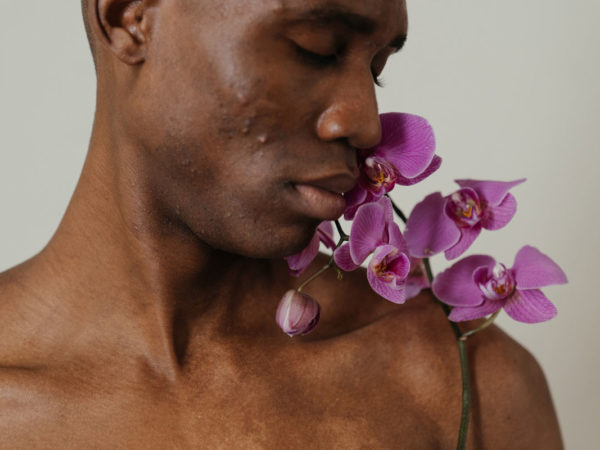 Topless man with acne holding purple orchids