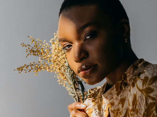 Black woman with the sunlight beaming on half of her face, holding a bunch of small yellow flowers to her cheek