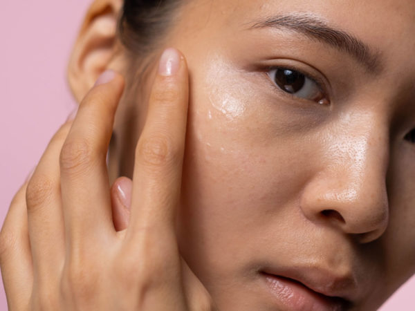 Close up of woman applying skincare on her cheek with pink background